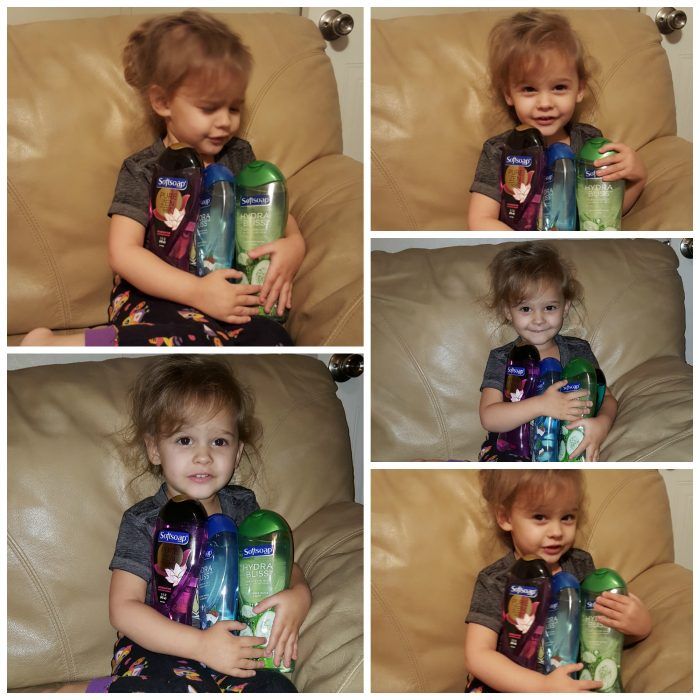 young girl holding 4 bottles of Softsoap Body Wash