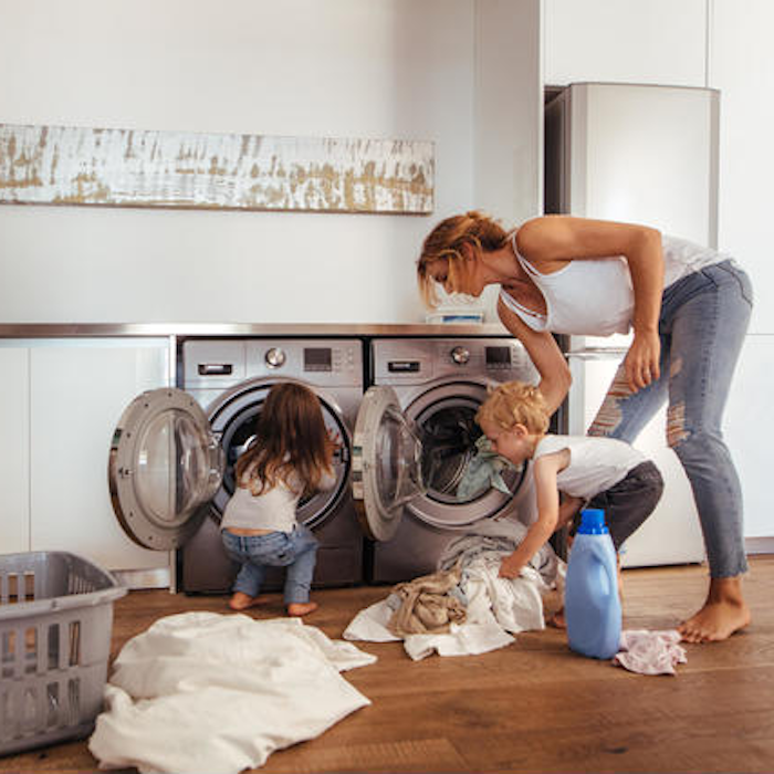 Kids helping Mom with chores around the house doing laundry