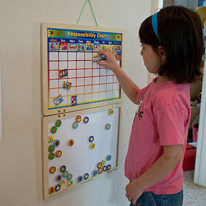 Small girl moving around pieces on a chore chart on the wall