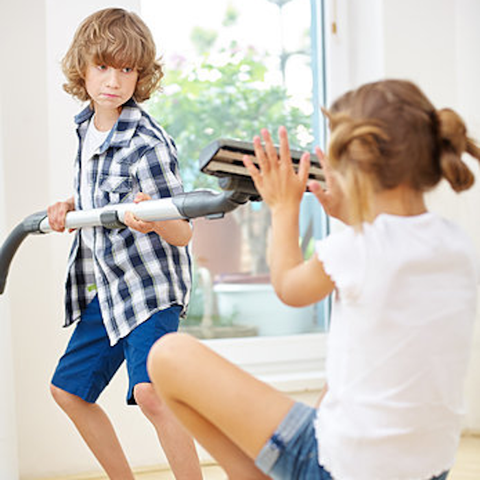 Brother taunting sister with vacuum cleaner as they do household chores